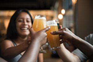 Øl bliver skålet i mod hinanden af glade mennesker