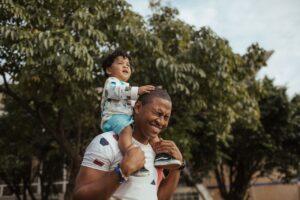 Mand bærer barn på skuldrene
