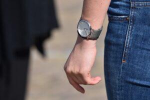 Mand har et ur på armen med blå jeans