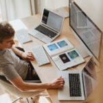 Mand arbejder på kontor med mange skærme og papirer